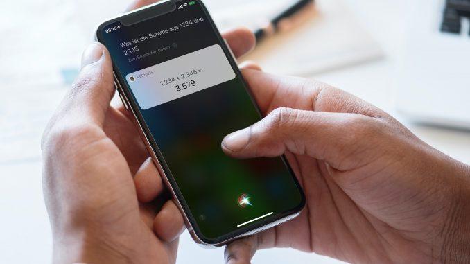 iPhone in einer Hand. Jemand lässt sich mittels Siri eine Mathe-Aufgaben berechnen.